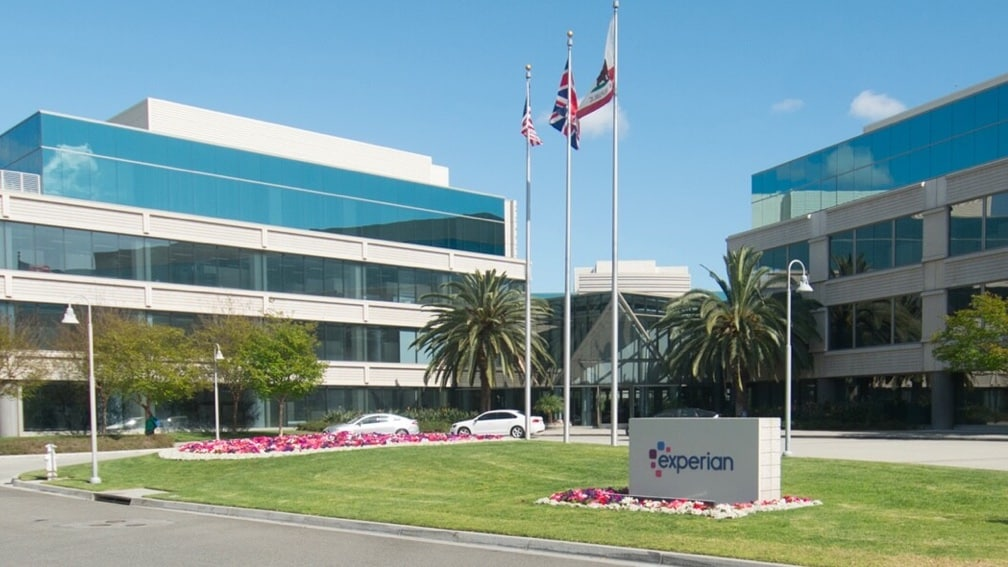 A view of the Experian office building in California on a sunny day with flags waving and palm trees