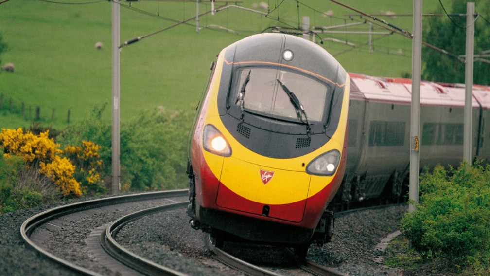 A Virgin Trains train is rounding a curve in the countryside